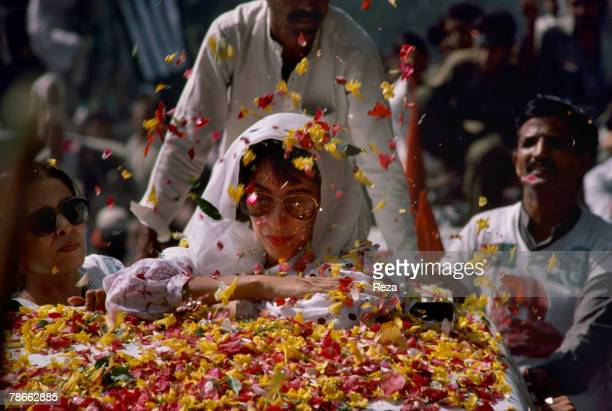 Supporters throw flower petals to greet Pakistan People's Party candidate Benazir Bhutto as she travels during the election campaign against current...