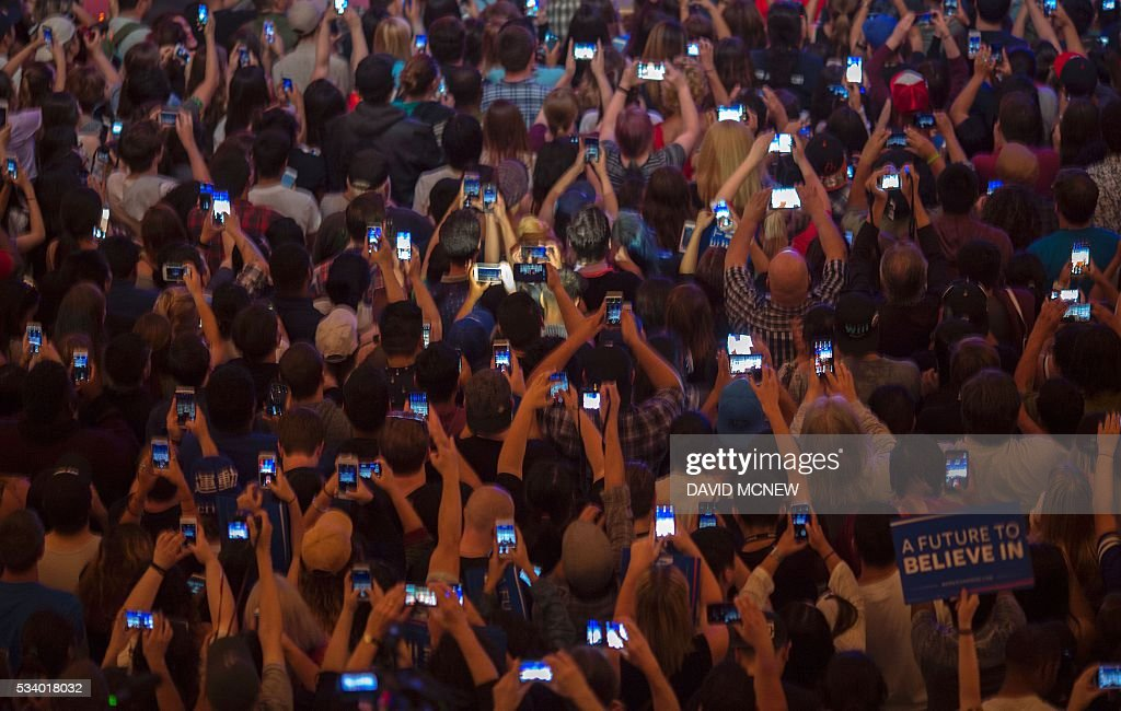 Supporters use smart phones to photograph Democratic presidential candidate Bernie Sanders during a campaign rally at the Riverside Municipal Auditorium on May 24, 2016 in Riverside, California. US presidential candidates have turned their attention to campaigning in earnest for the June 7th California primary election. / AFP / DAVID