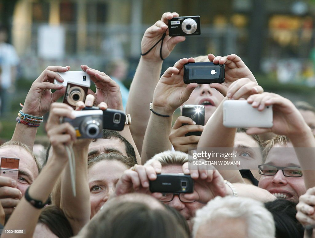 Supporters use their cameras and mobile phones including an iPhone as they try to catch pictures of their idols US actor Tom Cruise and US actress Cameron Diaz (both unseen) arriving on the red carpet for the premiere of their film 'Knight and Day' on July 21, 2010 in Munich, southern Germany. The movie will start in German cinemas on July 22, 2010.