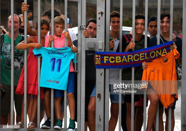 Supporters wait for the arrival of Barcelona's new player Ousmane Dembele outside the Camp Nou stadium in Barcelona French starlet Ousmane Dembele...