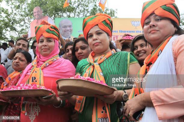 Supporters wait to welcome BJP National President Amit Shah while on his way in a procession from Sanganer Airport to party office on the first day...
