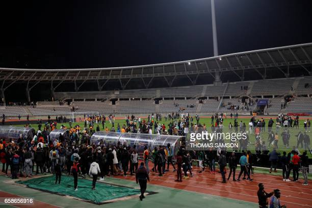 TOPSHOT Supporters walk on the pitch after inviding it leading the referee to bring the friendly football match Ivory Coast vs Senegal to a premature...