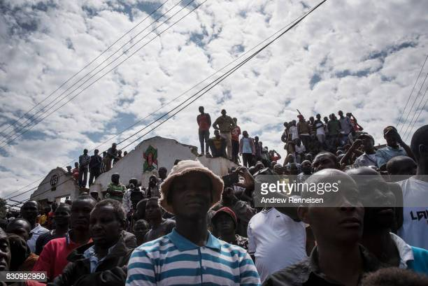 Supporters watch as opposition candidate Raila Odinga addresses a crowd in the Kibera slum on August 13 2017 in Nairobi Kenya A day prior...