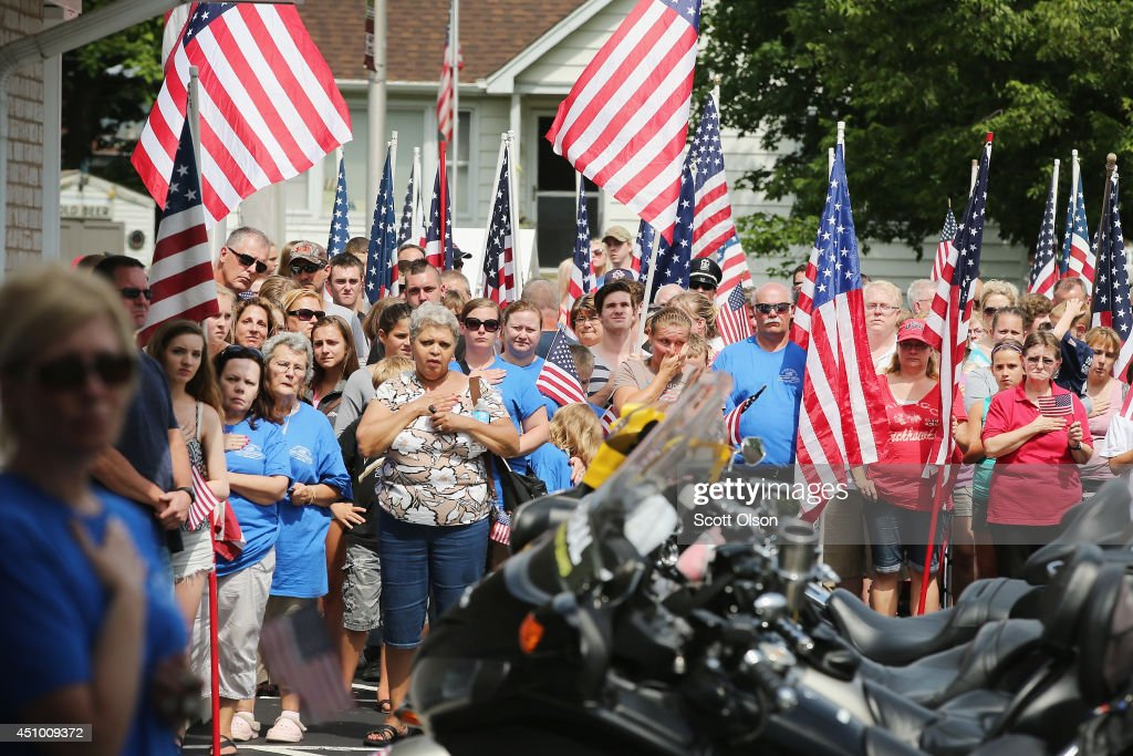 Supporters watch as the remains of Army Pfc. Aaron Toppen are carried into the funeral home on June 21, 2014 in Mokena, Illinois. Toppen, 19, was killed alongside four other American Soldiers and an Afghan soldier in a friendly fire airstrike during a firefight earlier this month in Afghanistan. His remains were flown into Chicago's Midway Airport today and escorted home to Mokena where he will be buried on Tuesday.