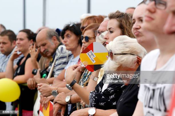 Supporters watch German Chancellor and head of the German Christian Democrats Angela Merkel speaking at an election rally at the headland known as...