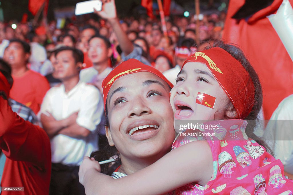 Supporters watch Myanmar's opposition National League for Democracy cheer in front of the NLD headquarters a day after the general election on...