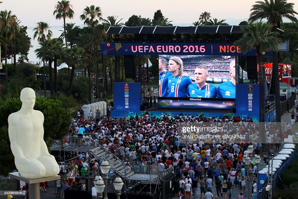 Supporters watch on a giant screen the Euro 2016 football match England vs Iceland, at the Nice Fanzone in Nice southeastern France, on June 27, 2016. / AFP / JEAN