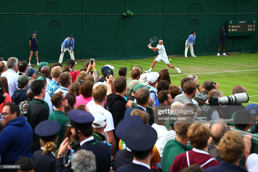 Supporters watch on as Marcus Willis of Great Britain plays a backhand shot during the Men's Singles first round match against Ricardas Berankis of Lithuania on day one of the Wimbledon Lawn Tennis Championships at the All England Lawn Tennis and Croquet Club on June 27th, 2016 in London, England.