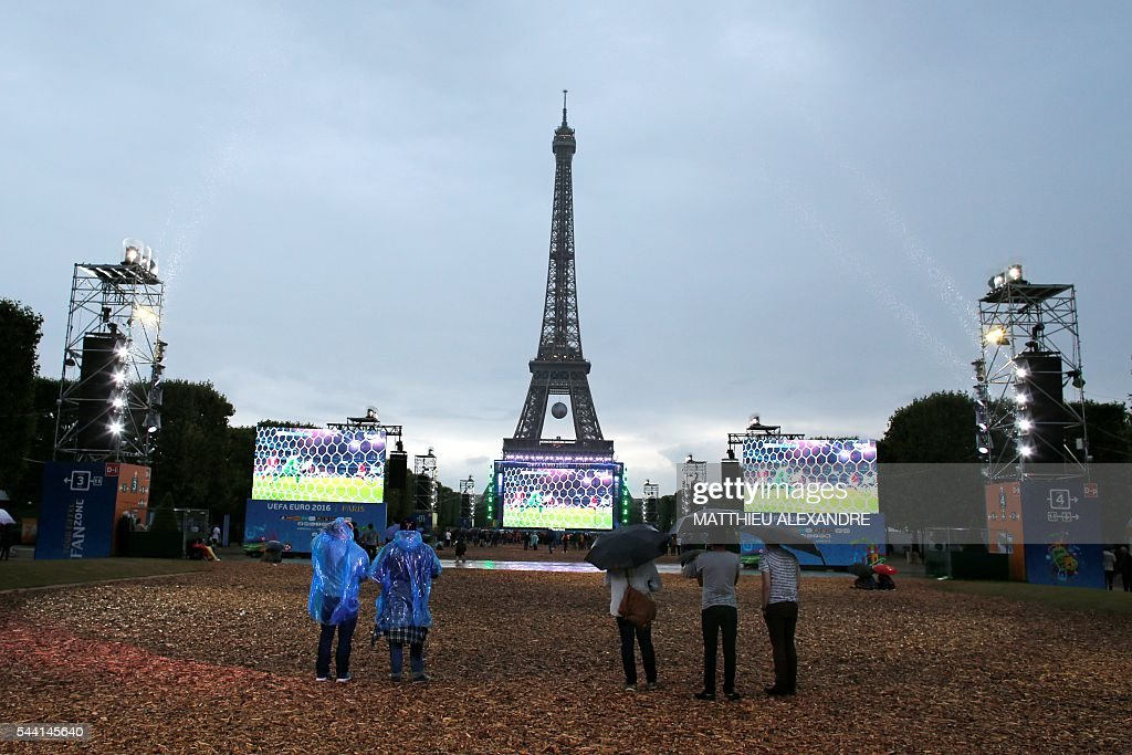 Supporters watch the Euro 2016 quarter-final football match between Wales and Belgium on a giant screen at the fan zone near the Eiffel Tower in Paris on July 1, 2016. / AFP / MATTHIEU