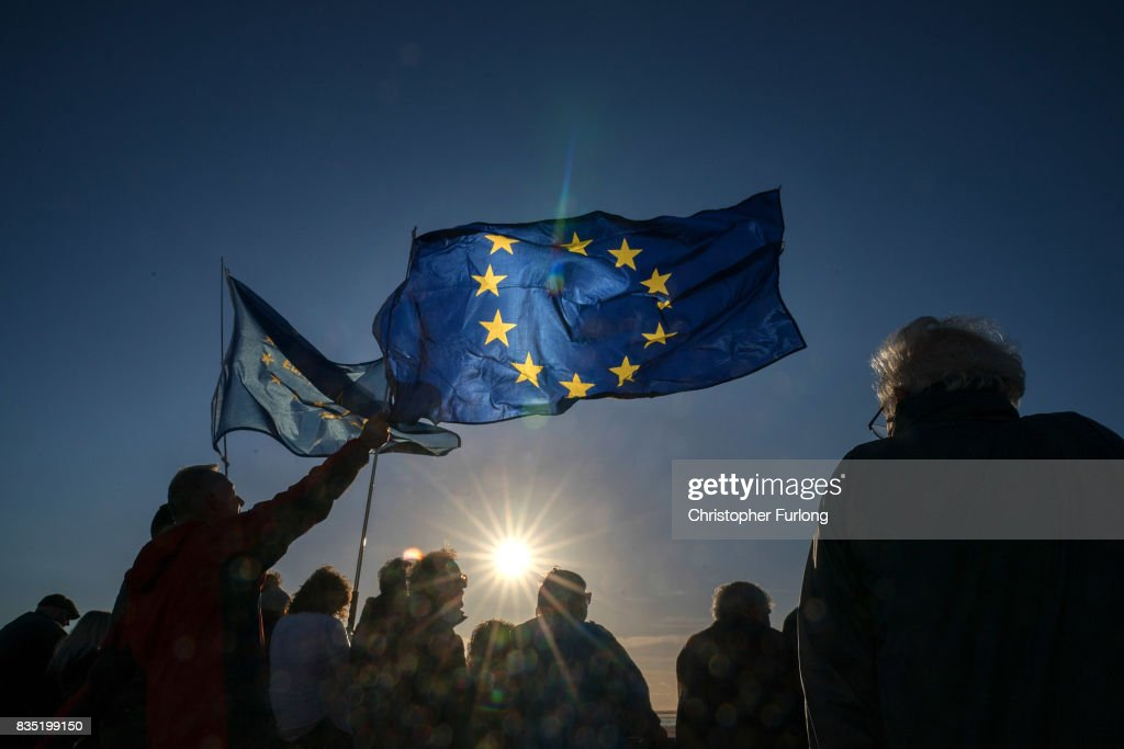 Supporters wave EU flags as they listen to Labour Party Leader Jeremy Corbyn during a rally on Southport Beach on August 18, 2017 in Southport, England. Jeremy Corbyn is in the north west as part of his UK wide tour visiting marginal seats.