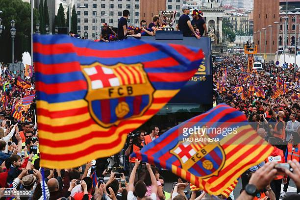 TOPSHOT Supporters wave FC Barcelona flags as the team parades on a bus through the streets of Barcelona to celebrate their 24th La Liga title in...