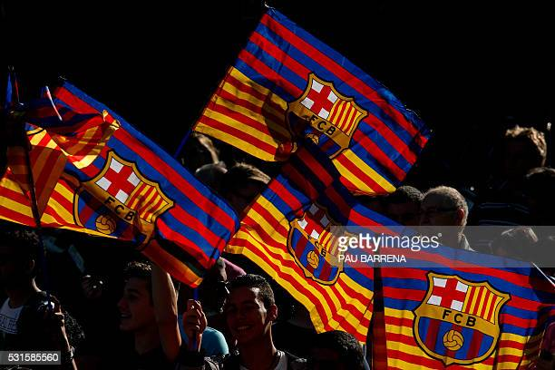 Supporters wave FC Barcelona's flags as they wait for the team parade through the streets of Barcelona to celebrate their 24th La Liga title in...