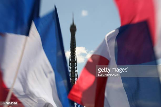 Supporters wave flags as the Eiffel tower is seen in the background before the start of a campaign meeting of France's incumbent president and Union...