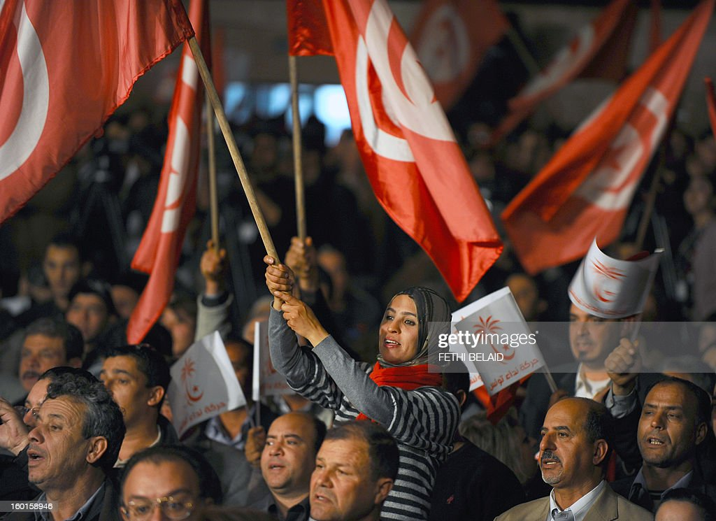 Supporters wave flags during a meeting as part of an open day to mark the first anniversary of the 'Nidaa Tounes' opposition party on January 27, 2013, at the Congress Hall of Tunis. Tunisian former prime minister and opposition leader, Beji Caid Essebsi has shown its support with the call of the prime minister Hamadi Jebali for a national dialogue and pointed out in his speech that the current government has failed on all fronts and that the change should be radical without stopping simply a cabinet reshuffle. AFP PHOTO / FETHI BELAID