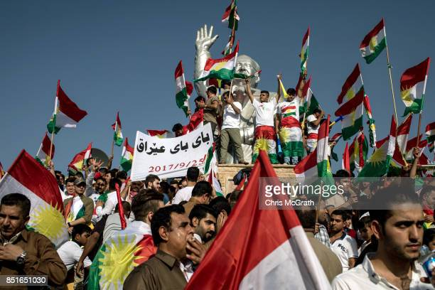 Supporters wave flags from the stadiom statue of Franso Hariri as the wait for the arrival of Kurdish President Masoud Barzani during a rally for the...