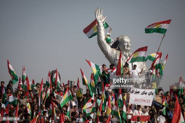 Supporters wave flags from the stadium statue of Franso Hariri as they wait for the arrival of Kurdish President Masoud Barzani during a rally for...