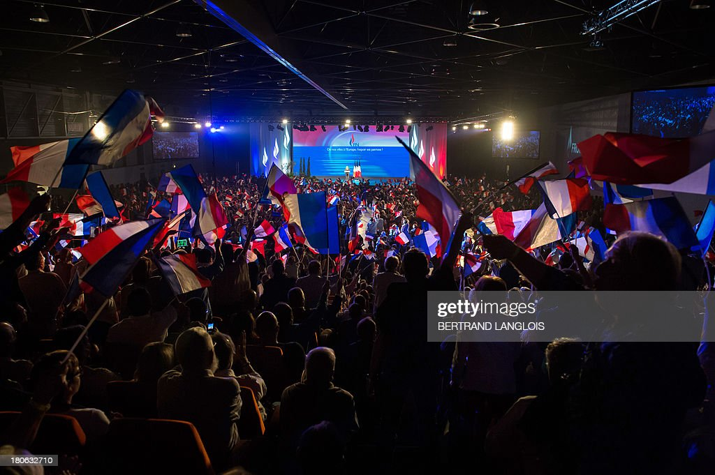 Supporters wave French flags as French far-right Front National (FN) party President Marine Le Pen delivers a speech during the FN summer congress on September 15, 2013 in Marseille, southern France. AFP PHOTO / BERTRAND LANGLOIS