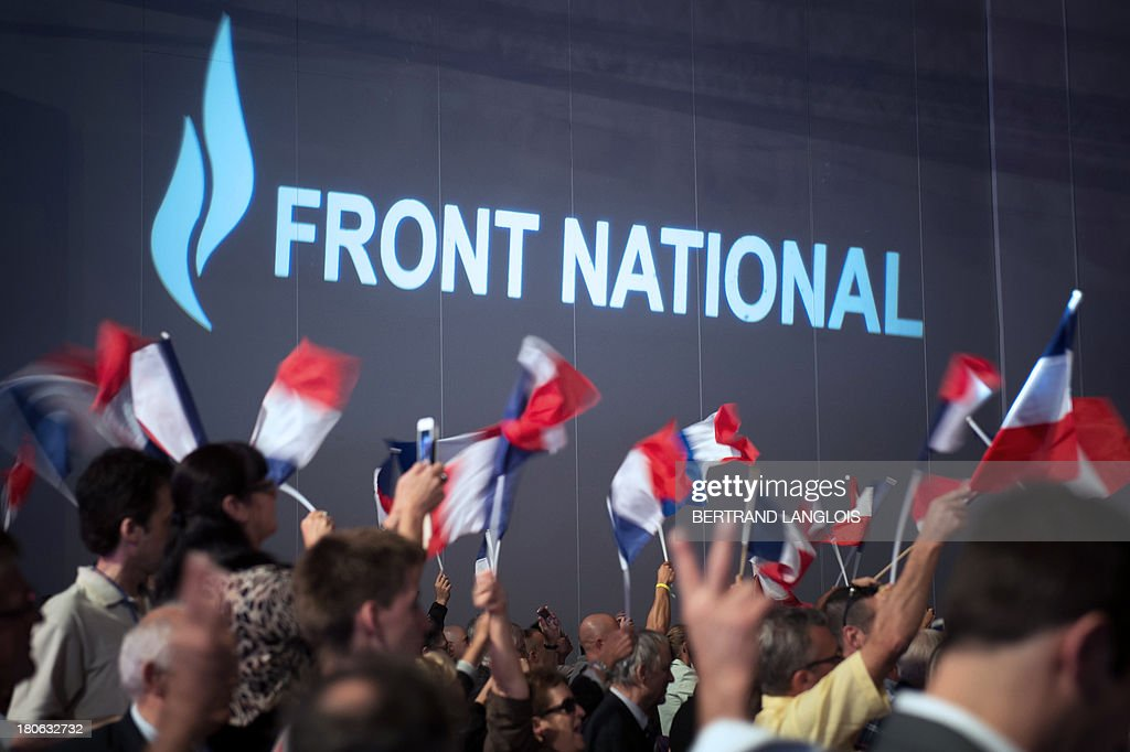 Supporters wave French flags as French far-right Front National (FN) party President Marine Le Pen delivers a speech during the FN summer congress on September 15, 2013 in Marseille, southern France.