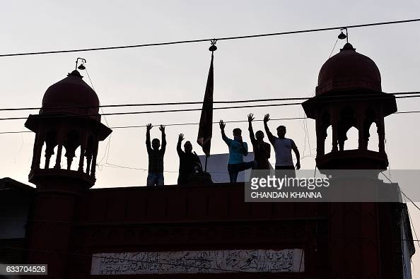 Supporters wave from a roof top as they attend a joint election campaign rally by the Uttar Pradesh state chief minister and Congress party vice...