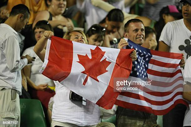 Supporters wave national flags as they cheer for James Blake of the US and Frank Dancevic of Canada during their men's singles match at the...