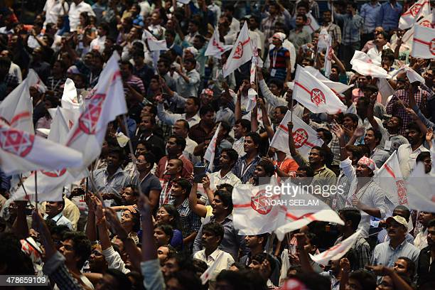Supporters wave party flags as Indian Telugu film actor Pawan Kalyan announces the launch of his new political party Jana Sena at the Hyderabad...