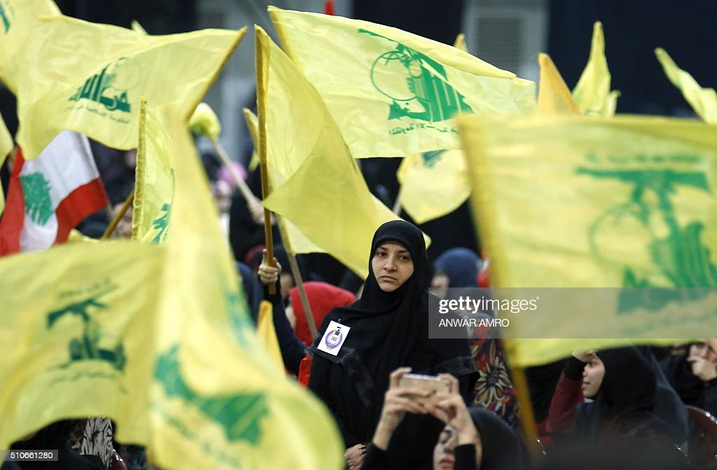 Supporters wave the flag of Lebanon's Shiite movement Hezbollah as they watch the movement's leader Hassan Nasrallah give a televised speech from an...