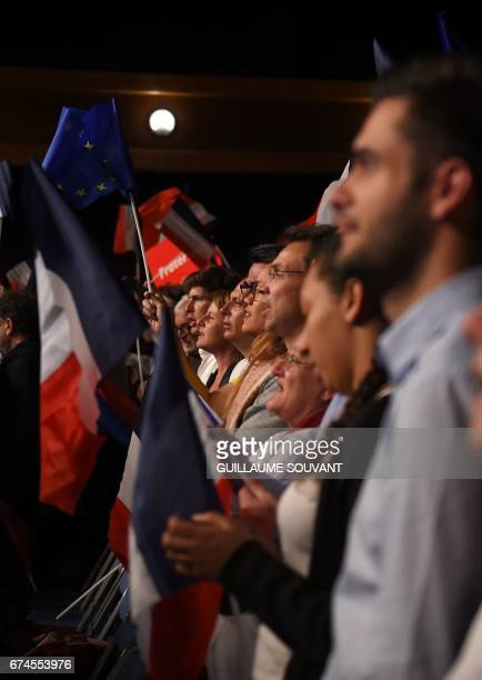 Supporters wave the national flag as French presidential election candidate for the En Marche movement Emmanuel Macron gives a speech ahead of the...