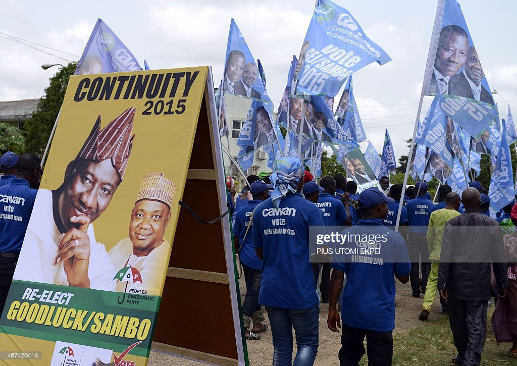 Supporters waving flags walk past a campaign sign to mobilize support for the re-election of Nigerian President <a gi-track='captionPersonalityLinkClicked' href=/galleries/search?phrase=Goodluck+Jonathan&family=editorial&specificpeople=4124968 ng-click='$event.stopPropagation()'>Goodluck Jonathan</a> and candidate of the ruling Peoples Democratic Party (PDP) during a rally in Akure, Ondo State in southwestern Nigeria, on March 24, 2015. Africa's most populous country and top economy, Nigeria, holds general elections on March 28 -- the fifth since civilian rule was restored in 1999.