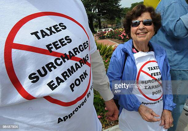Supporters wear tshirts encouraging the Federal Government to reduce spending as they attend a Tea Party rally to coincide with the tax filing...
