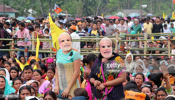 BJP supporters wearing masks of Prime Minister Narendra Modi during his election campaign rally at Birpara on April 7 2016 in Dooars India West...