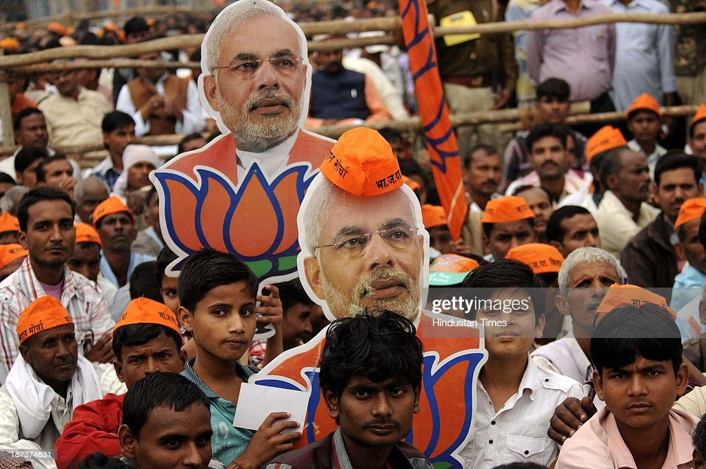 BJP supporters with cutouts of BJP prime ministerial candidate Narendra Modi during his rally at Begumpur Sohrawa village on November 8, 2013 in Bahraich, India. In a hard-hitting attack on the Congress, Bahujan Samaj Party and Samajwadi Party at a rally here, Modi said the three parties had similar DNA, and urged people of Uttar Pradesh to give a decisive mandate to the BJP in the 2014 Lok Sabha polls.