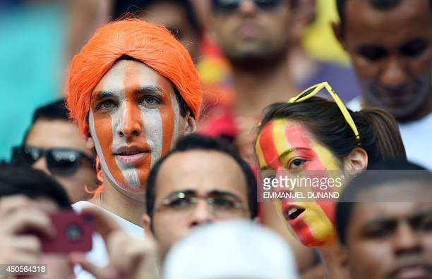 Supporters with their faces painted with the colors of the Spanish and the Netherland's flag wait for the start of a Group B football match between...