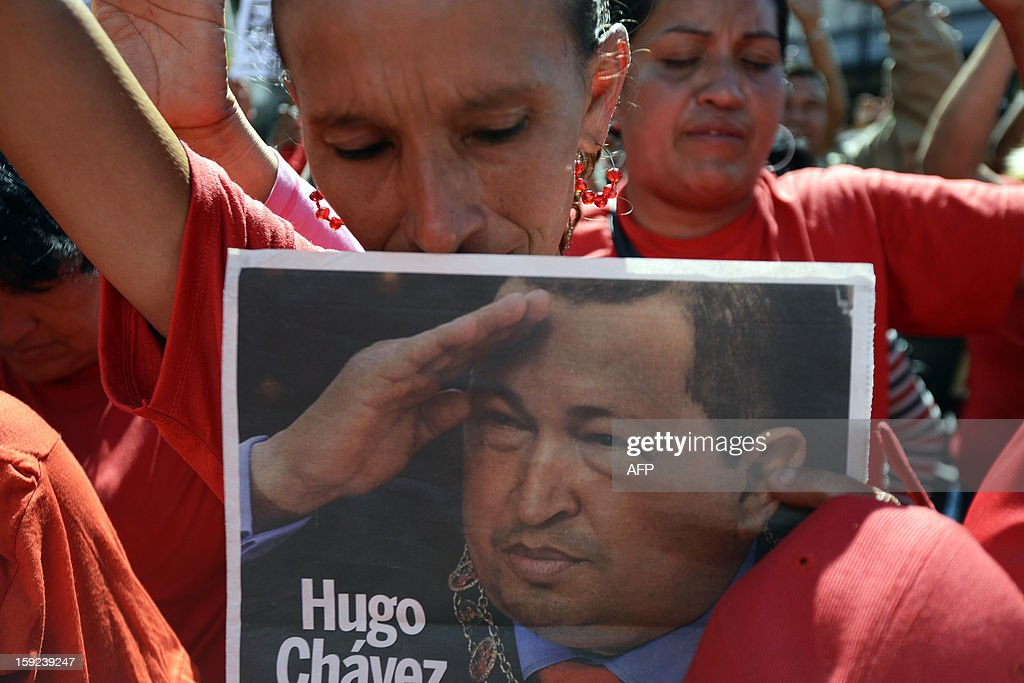 Supportes of Venezuelan President Hugo Chavez pray for his health during a meeting outside Miraflores Presidential Palace in Caracas on January 10, 2013. With Chavez ailing and absent, Venezuela's leftist government launches a new presidential term with a display of popular support on the day he was to be inaugurated. The Supreme Court cleared the cancer-stricken president to indefinitely postpone his re-inauguration and said his existing administration could remain in office until he is well enough to take the oath.AFP PHOTO/Leo RAMIREZ