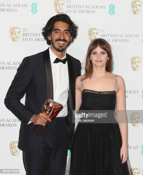 Supporting Actor winner Dev Patel and presenter Felicity Jones pose in the winners room during the 70th EE British Academy Film Awards at Royal...
