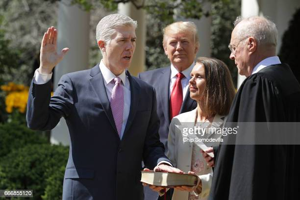 S Supreme Court Associate Justice Anthony Kennedy administers the judicial oath to Judge Neil Gorsuch as his wife Marie Louise Gorshuch holds a bible...