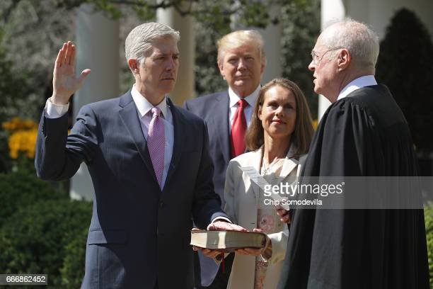 S Supreme Court Associate Justice Anthony Kennedy administers the judicial oath to Judge Neil Gorsuch as his wife Marie Louise Gorsuch holds a bible...