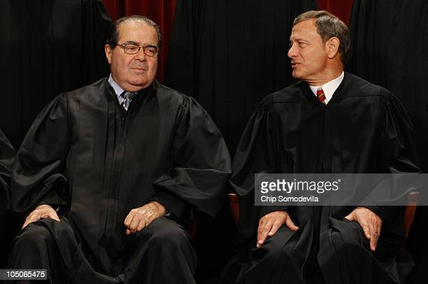 S Supreme Court Associate Justice Antonin Scalia and Chief Justice John Roberts talk while posing for photographs in the East Conference Room at the...