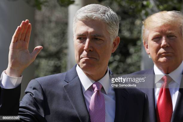 S Supreme Court Associate Justice Judge Neil Gorsuch takes the judicial oath as President Donald Trump looks on during a ceremony in the Rose Garden...
