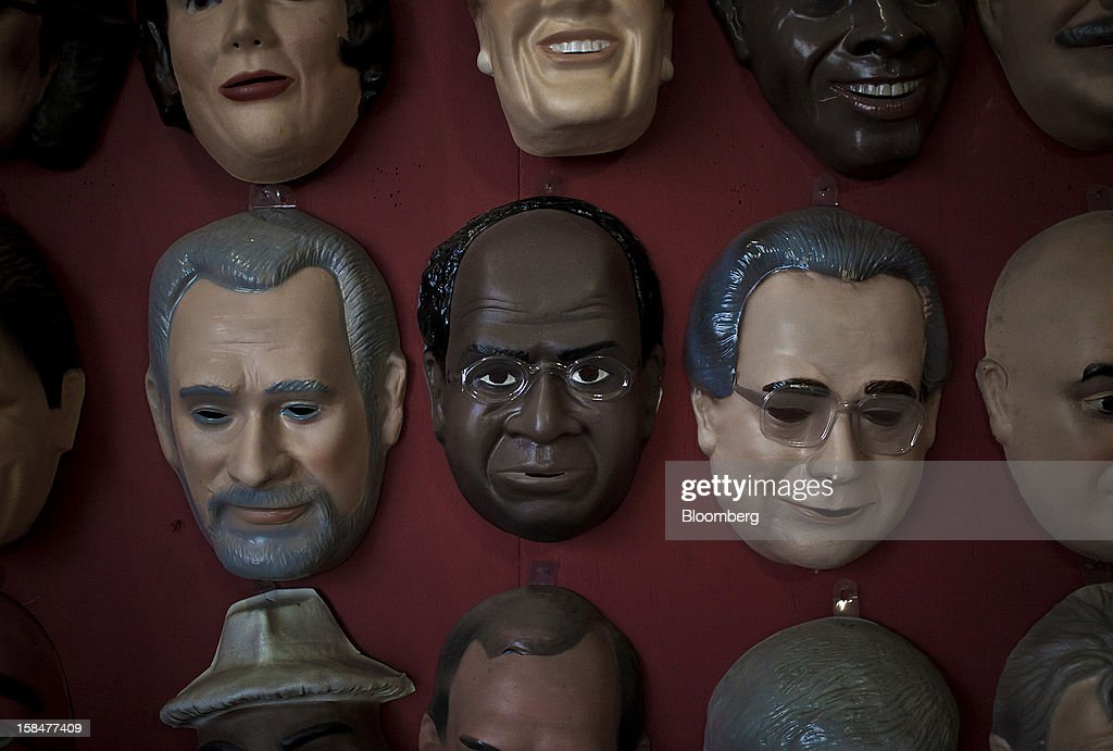A Supreme Court Chief Justice Joaquim Barbosa Carnival mask, center, hangs on a wall at the Mascaras Condal factory in Sao Goncalo, Brazil, on Monday, Dec. 17, 2012. In a uniquely Brazilian measure of star status, Barbosa masks will be among the most popular during the Carnival celebration in February, according to Rio de Janeiro's O Globo newspaper.Photographer: Dado Galdieri/Bloomberg via Getty Images
