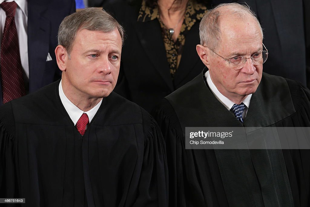 U.S. Supreme Court Chief Justice <a gi-track='captionPersonalityLinkClicked' href=/galleries/search?phrase=John+Roberts+-+17th+Chief+Justice+of+the+United+States&family=editorial&specificpeople=2220360 ng-click='$event.stopPropagation()'>John Roberts</a> (L) and Associate Justice <a gi-track='captionPersonalityLinkClicked' href=/galleries/search?phrase=Anthony+Kennedy+-+Judge&family=editorial&specificpeople=220874 ng-click='$event.stopPropagation()'>Anthony Kennedy</a> listen to President Barack Obama deliver the State of the Union address to a joint session of Congress in the House Chamber at the U.S. Capitol on January 28, 2014 in Washington, DC. In his fifth State of the Union address, Obama is expected to emphasize on healthcare, economic fairness and new initiatives designed to stimulate the U.S. economy with bipartisan cooperation.