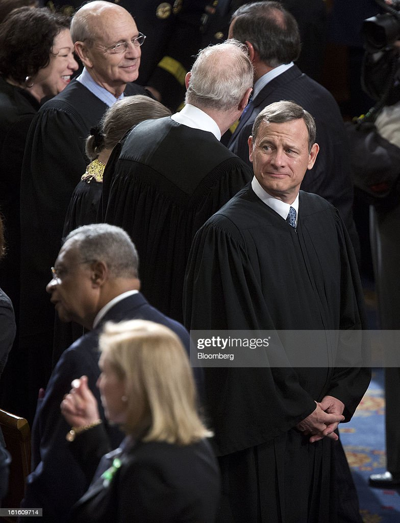 Supreme Court Chief Justice John Roberts, right, looks on before U.S. President Barack Obama's State of the Union address to a joint session of Congress at the Capitol in Washington, D.C., U.S., on Tuesday, Feb. 12, 2013. Obama called for raising the federal minimum wage to $9 an hour and warned he'll use executive powers to get his way on issues from climate change to manufacturing if Congress doesn't act, laying out an assertive second-term agenda sure to provoke Republicans. Photographer: Joshua Roberts/Bloomberg via Getty Images