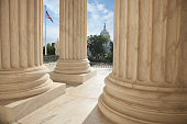 Close up of the columns  of the Supreme Court building with an American flag and the US Capitol in the background