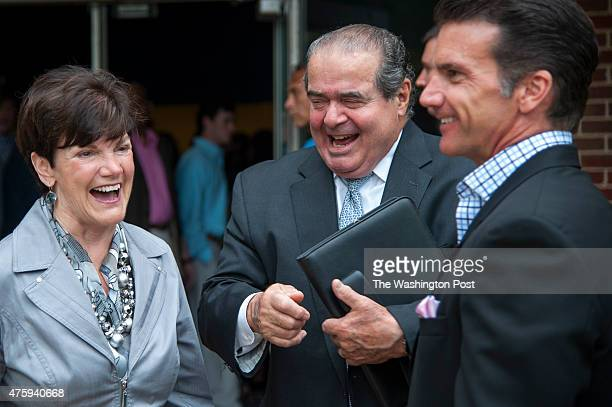 Supreme Court Justice Antonin Scalia center laughs with Sharon Taskey and her son Todd Taskey after a short conversation about baseball loyalties...