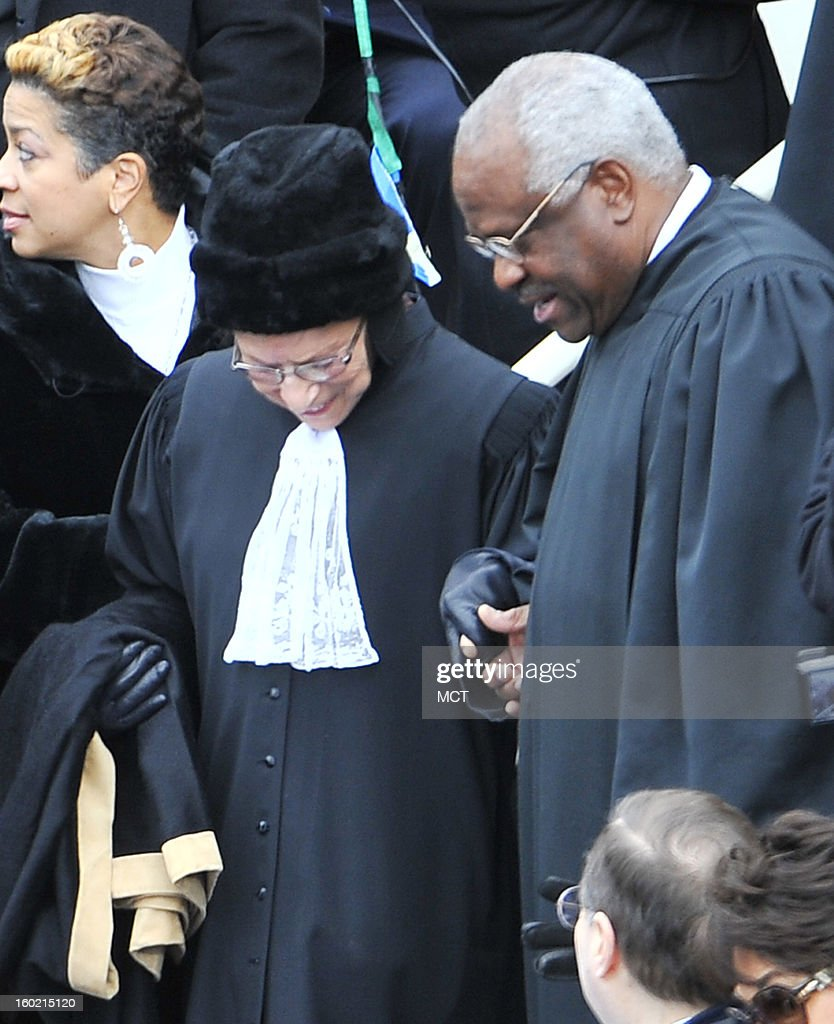 Supreme Court Justice Clarence Thomas helps fellow Supreme Court Justice Ruth Bader Ginsberg to her seat at the swearing-in of Barack Obama on the West Front of the U.S. Capitol, Monday, January 21, 2013 in Washington, D.C. Barack Obama was re-elected for a second term as President of the United States.