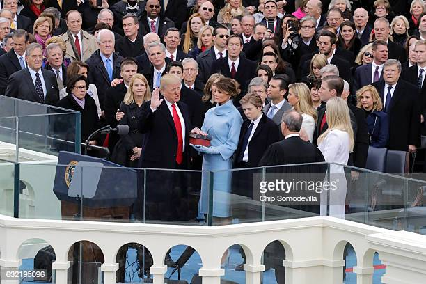 Supreme Court Justice John Roberts administers the oath of office to US President Donald Trump as his wife Melania Trump holds the Bible and his son...