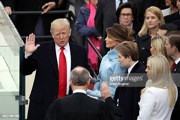 Supreme Court Justice John Roberts administers the oath of office to US President Donald Trump as his wife Melania Trump holds the Bible on the West...