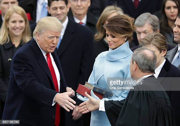 Supreme Court Justice John Roberts congratulates US President Donald Trump after administering the oath of office as his wife Melania Trump holds the...