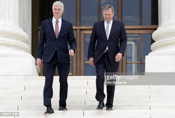 Supreme Court Justice Neil Gorsuch walks down the steps of the Supreme Court with Chief Justice John Roberts following his official investiture at...