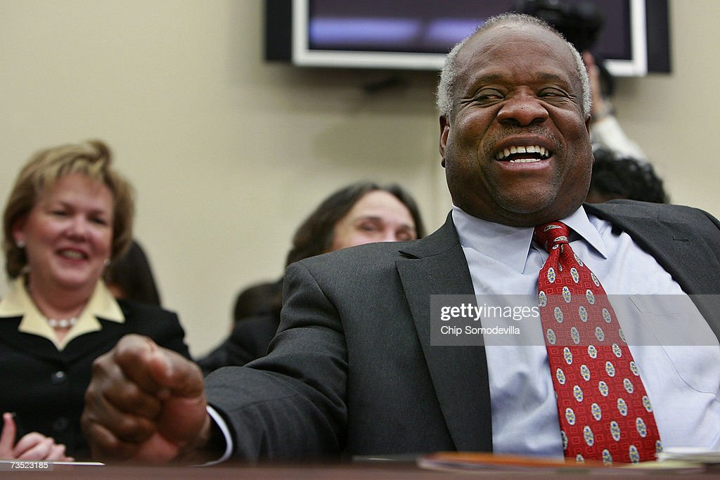 U.S. Supreme Court Justices Clarence Thomas laughs at a joke about baseball told between members of the House Financial Services and General Government Subcommittee while he testified before the subcommittee on Capitol Hill March 8, 2007 in Washington, DC. Thomas and fellow Justice Anthony Kennedy spoke about concerns with the ongoing remodeling of the court building, the reduction of paperwork due to electronic media and the disparity of pay between federal judges and lawyers working in the private sector.