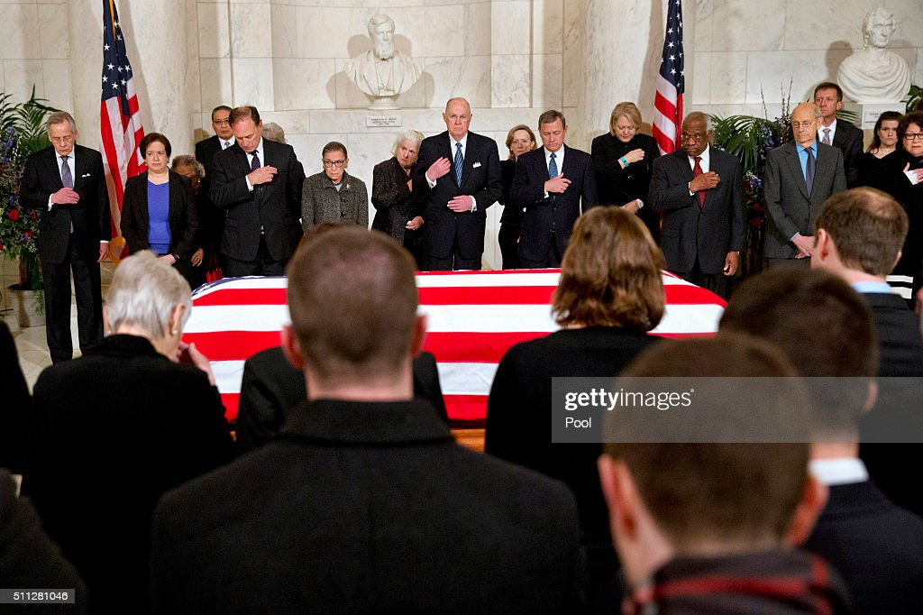 Supreme Court Justices make the sign of the cross during prayers at a private ceremony in the Great Hall of the Supreme Court where late Supreme Court Justice Antonin Scalia lies in repose on February 19, 2016 in Washington, DC. From back left are Counselor to the Chief Justice Jeffrey Minear, and Supreme Court Justices Elena Kagan, Samuel Anthony Alito, Jr., Ruth Bader Ginsburg, Anthony M. Kennedy, Chief Justice John G. Roberts, Jr., Clarence Thomas, Stephen G. Breyer, and Sonia Sotomayor. Justice Scalia will lie in repose in the Great Hall of the high court where visitors will pay their respects.